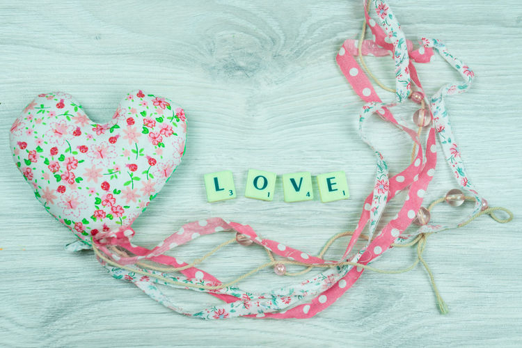 a heart with the word love next to it Love Valentine Valentine's Day  Wedding Close-up Communication Day Heart Shape High Angle View Indoors  Love Message No People Single Word Text Western Script White Wooden Texture