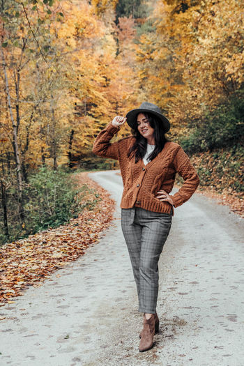 Front view of young woman on road in autumn, fall. outdoors, lifestyle, fashion.