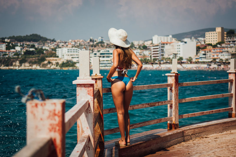 Rear view of woman wearing bikini while looking at sea