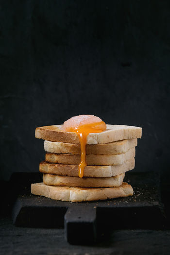 Stack of toasts bread with flowing sugared yolk on black wooden cutting board over black textured background. Breakfast Dessert Egg Yolk Sugar Toast Black Background Bread Cutting Board Egg Food Food And Drink Indulgence Ready-to-eat Sugared Yolk Sweet Food Table Toasted Bread Unhealthy Eating White Bread Yolk