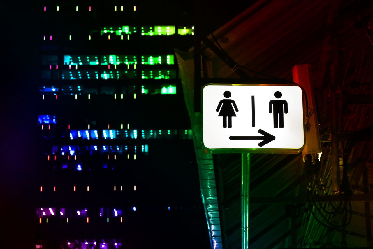 communication, illuminated, sign, night, guidance, text, information, no people, human representation, information sign, representation, symbol, lighting equipment, western script, indoors, male likeness, architecture, arrow symbol, directional sign, green color, light, restroom sign, nightlife