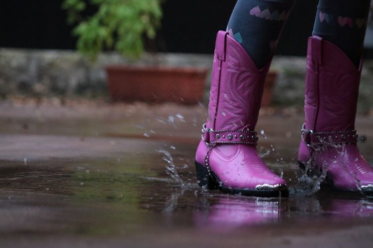 Low Section Of Woman Girl Pink Cowboy Boot On Wet Street