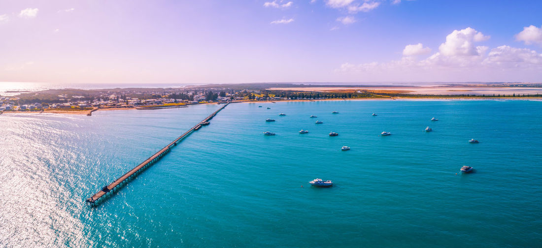 Wide aerial panorama of beachport jetty and moored boats at sunset in south australia