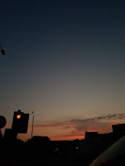 Silhouette of road signal against sky during sunset