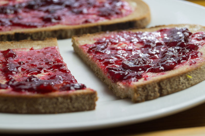 Close-up of brown breads with cherry jam on plate