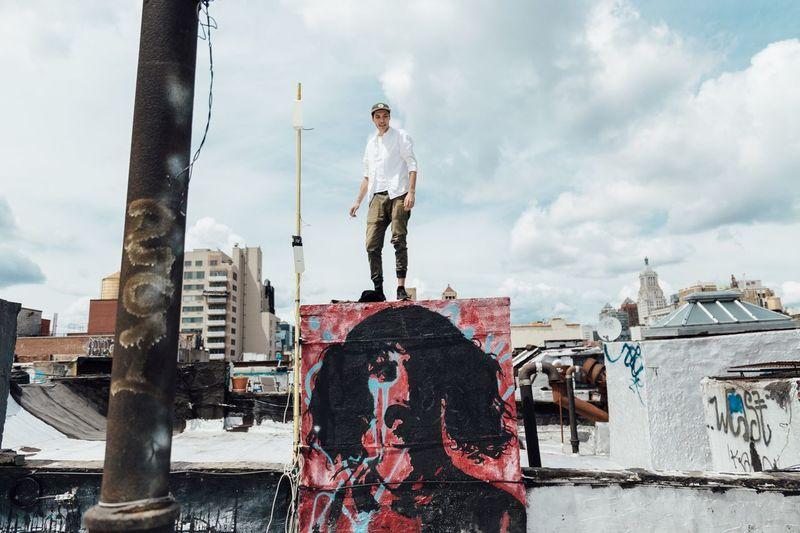 Full length of man standing against sky in city