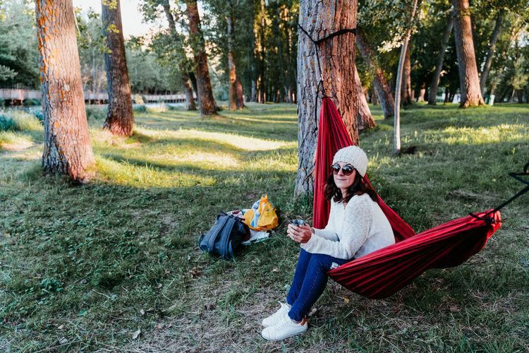 Woman lying on hammock in forest