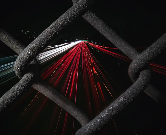 Light trails seen through chainlink fence at night