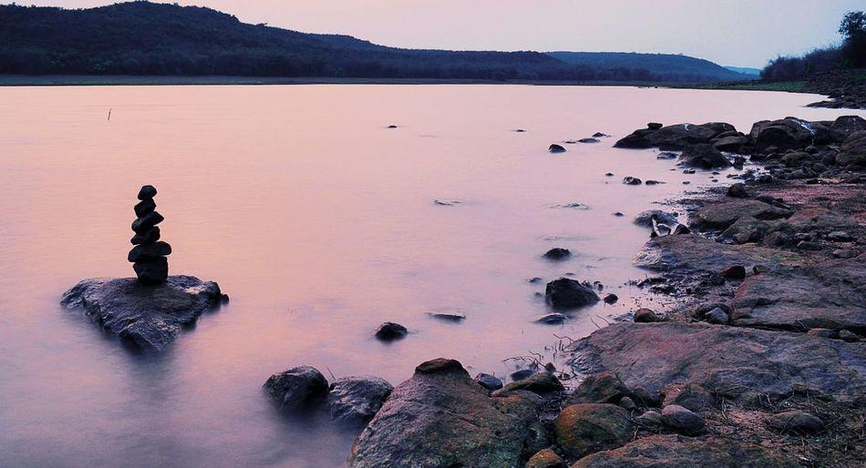 Stack of rocks in lake during sunset