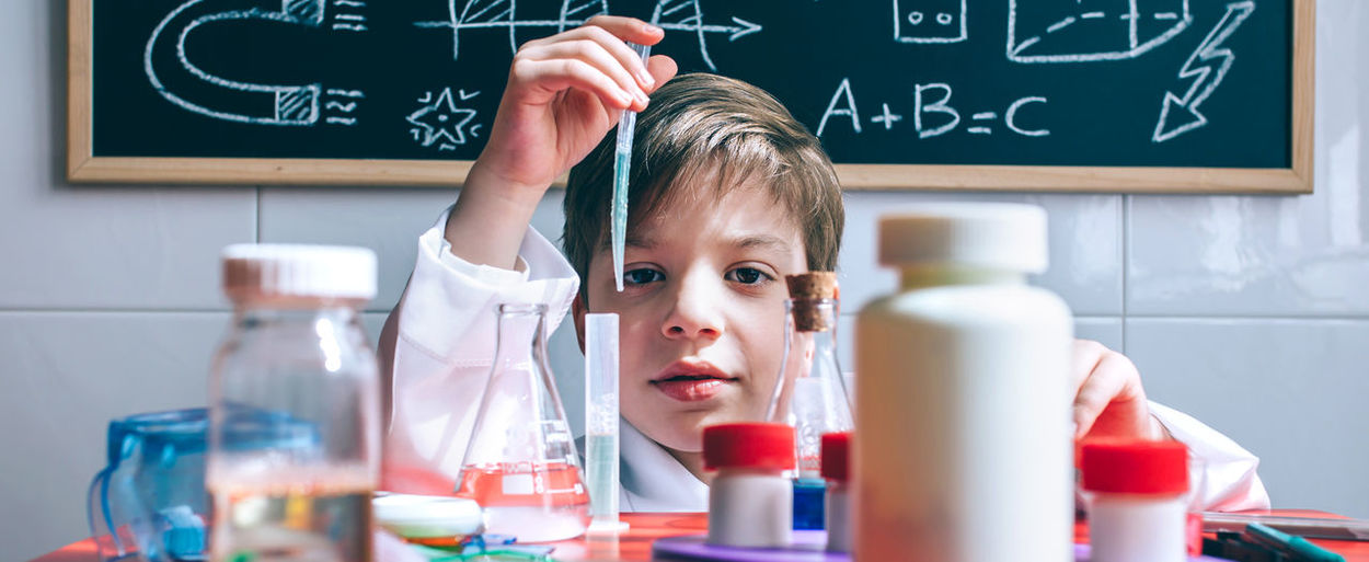 Portrait Of Cute Boy Examining Chemical In Classroom