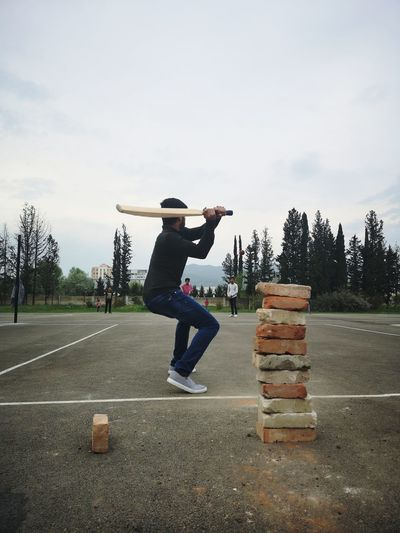 Full length of man playing cricket on road against sky