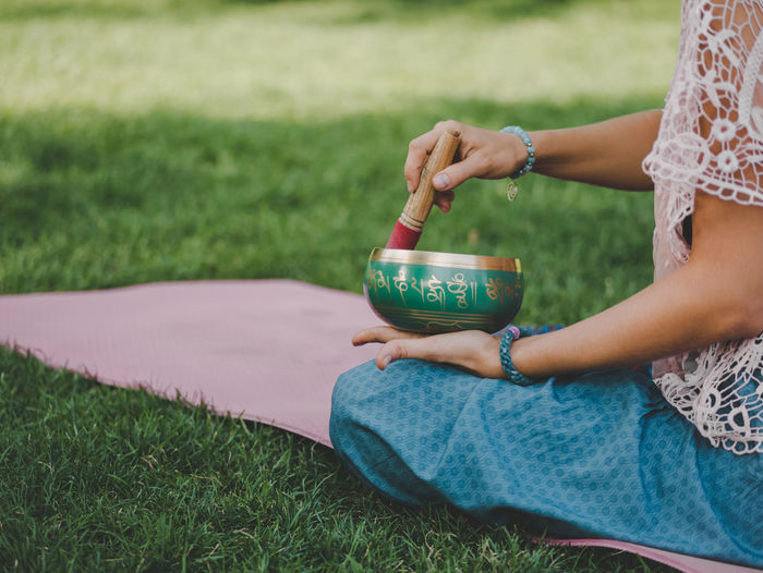 Midsection of young woman holding bowl while sitting on grassy field
