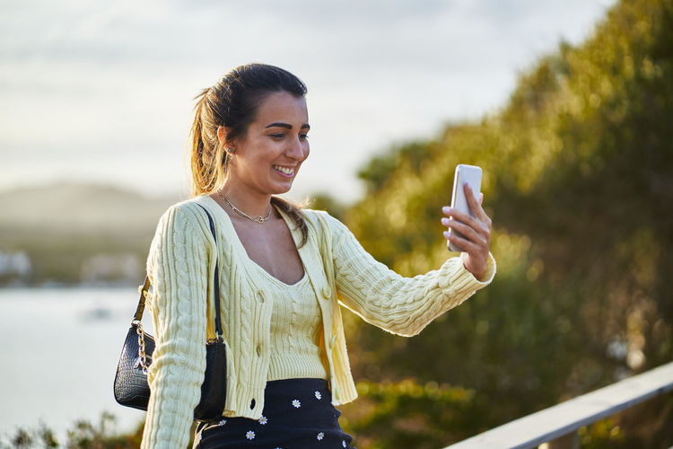 Smiling young woman using phone while standing outdoors