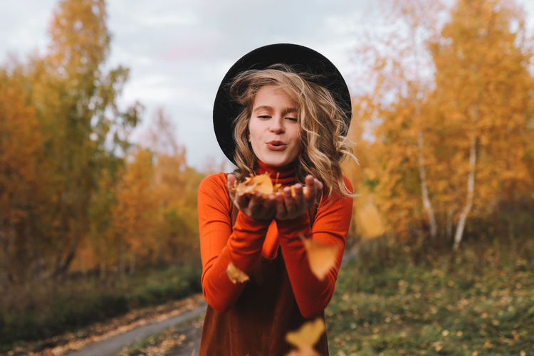 A pretty girl enjoys solitude drinks coffee walks in the autumn forest in nature in fall