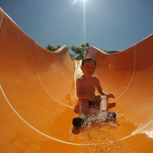 Low angle view of shirtless boy on water slide against clear sky