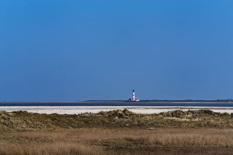 Scenic view of land and westerheversand lighthouse in remote