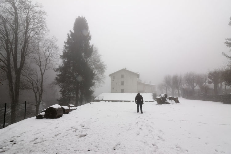 Rear view of man walking on snow covered houses