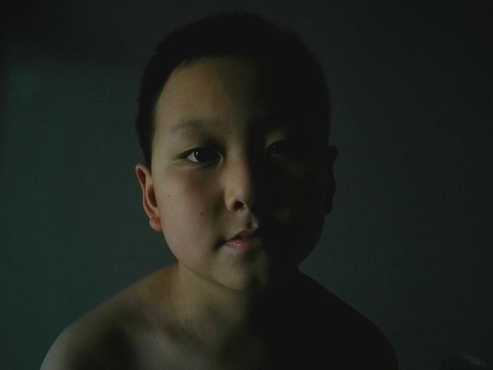 Portrait Of Shirtless Boy Against Black Background