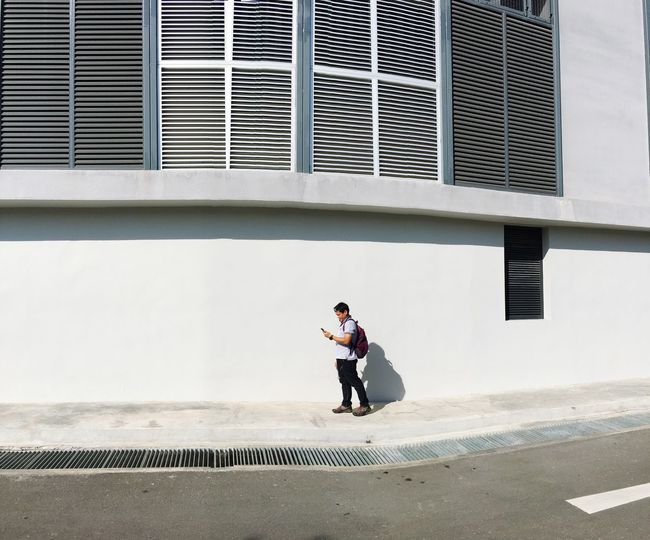 Man standing on footpath against building in city