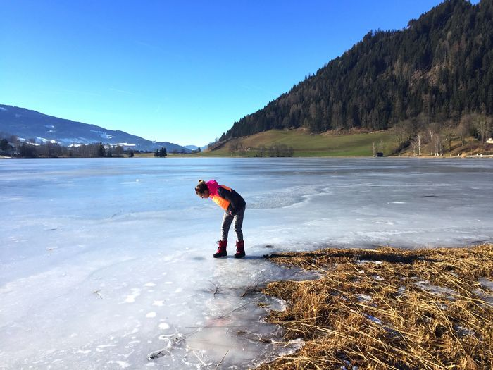 Full Length Of Woman Standing On Frozen Lake Against Clear Blue Sky