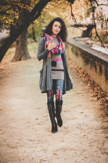 Full Length Portrait Of Young Woman Walking On Footpath