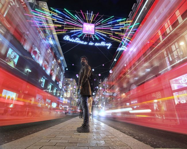 Blurred motion of woman standing on illuminated city at night