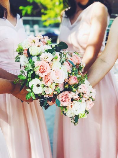 Midsection of bridesmaid holding bouquet