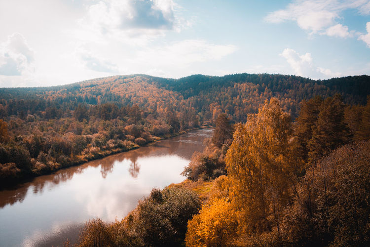 Scenic view of lake in forest against sky during autumn