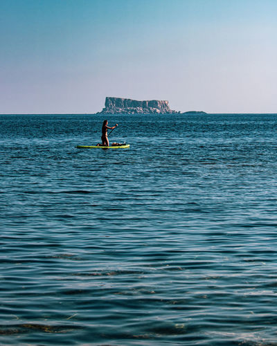 Scenic view of sea against clear sky with a lady on a raft