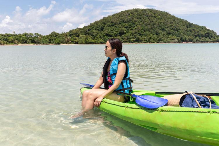 Full length of woman in boat on lake against sky