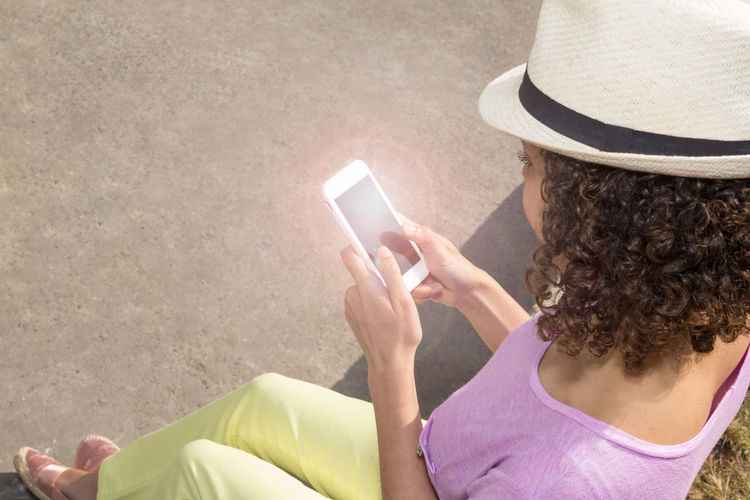 High angle view of woman using phone while sitting outdoors