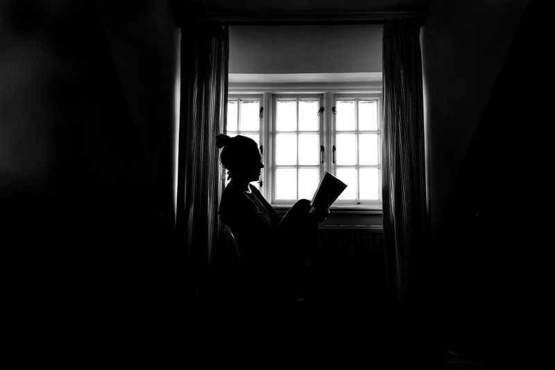 Side View Of Woman Reading Book By Window