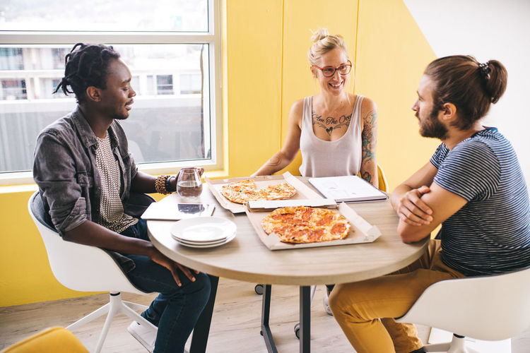 Friends having pizza while sitting in restaurant