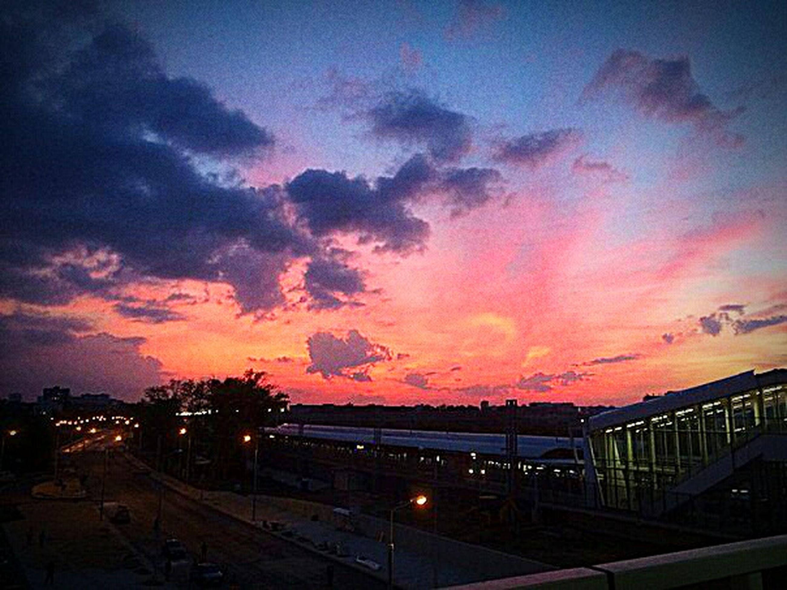 sunset, illuminated, sky, cloud - sky, dusk, cloud, scenics, beauty in nature, dramatic sky, majestic, city life, atmospheric mood, outdoors, romantic sky, dark, tranquil scene, atmosphere, orange color, nature, modern, moody sky