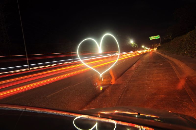 Blurred Motion Of Woman And Heart Shape Light Painting On Road Seen Through Car Windshield At Night