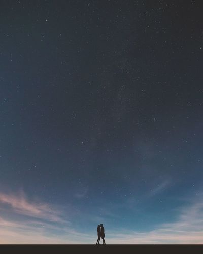 Silhouette couple kissing against sky at night
