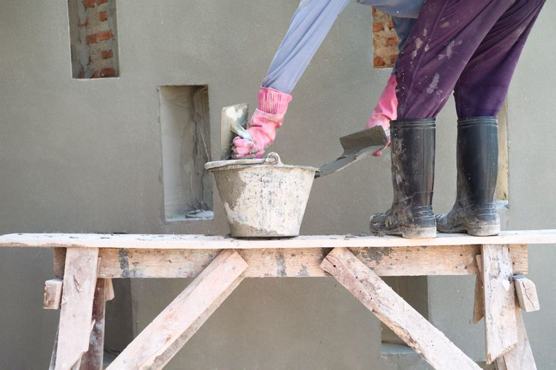 Worker stands on the wooden scaffolding and plasters the cement at the construction site.