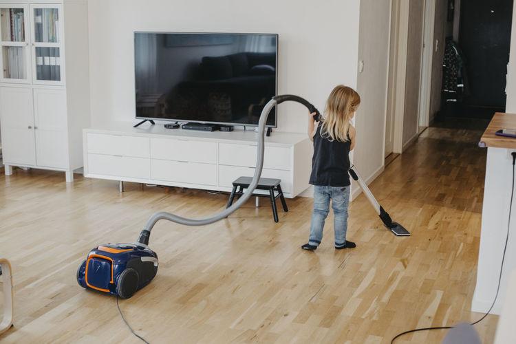 Woman using laptop on hardwood floor at home