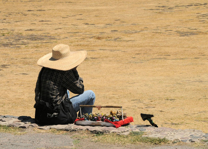 This vendor is taking a break at the Pyramids in Teotihuacan Desert Hot Isolated Lonely Long Day Mexico Onyx Pyramids Salesman Trinkets Day Hat Obsidian One Person Outdoors People Rule Of Thirds Sitting Sun Sun Hat Tired Vendor