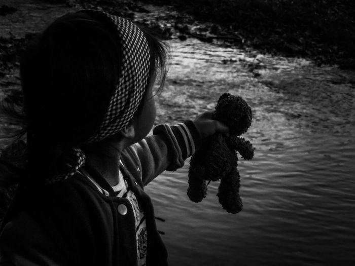 Little Girl Holding Teddy Bear Over River