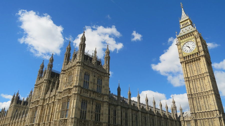 Low angle view of big ben against cloudy sky in city