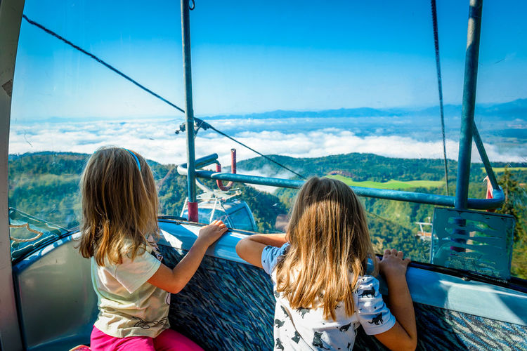 Girls traveling in overhead cable car against sky