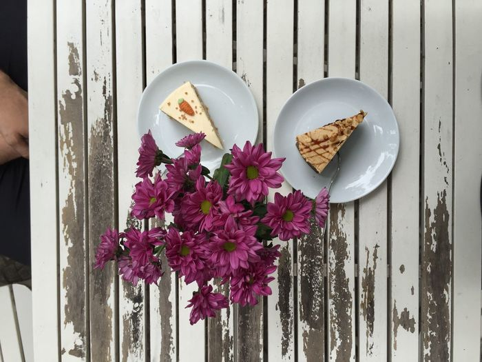 High Angle View Of Carrot Cake In Plates By Flowers On Table