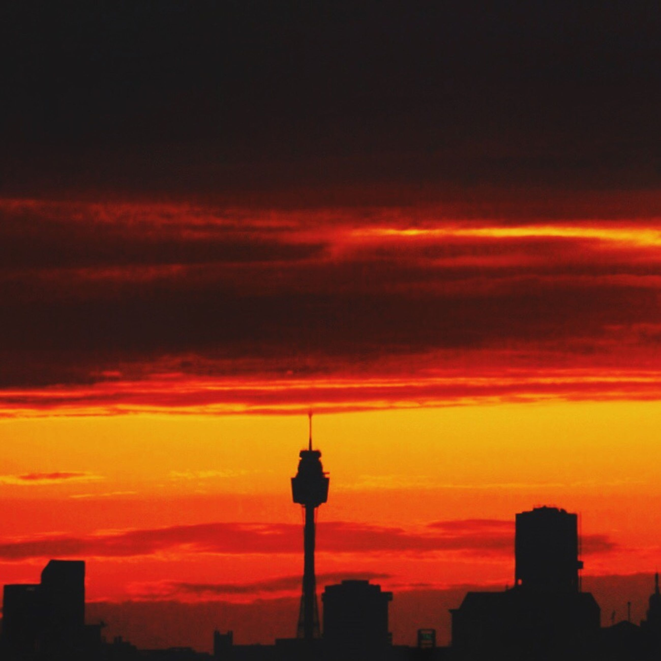 sunset, architecture, built structure, building exterior, communications tower, city, spire, tourism, orange color, sky, travel destinations, tall - high, tower, cloud - sky, romantic sky, fernsehturm, television tower, silhouette, travel, capital cities, high section, skyscraper, red, vibrant color, famous place, dramatic sky, culture, scenics, cloud, international landmark, sunbeam, outdoors, atmosphere, majestic, nature, office building