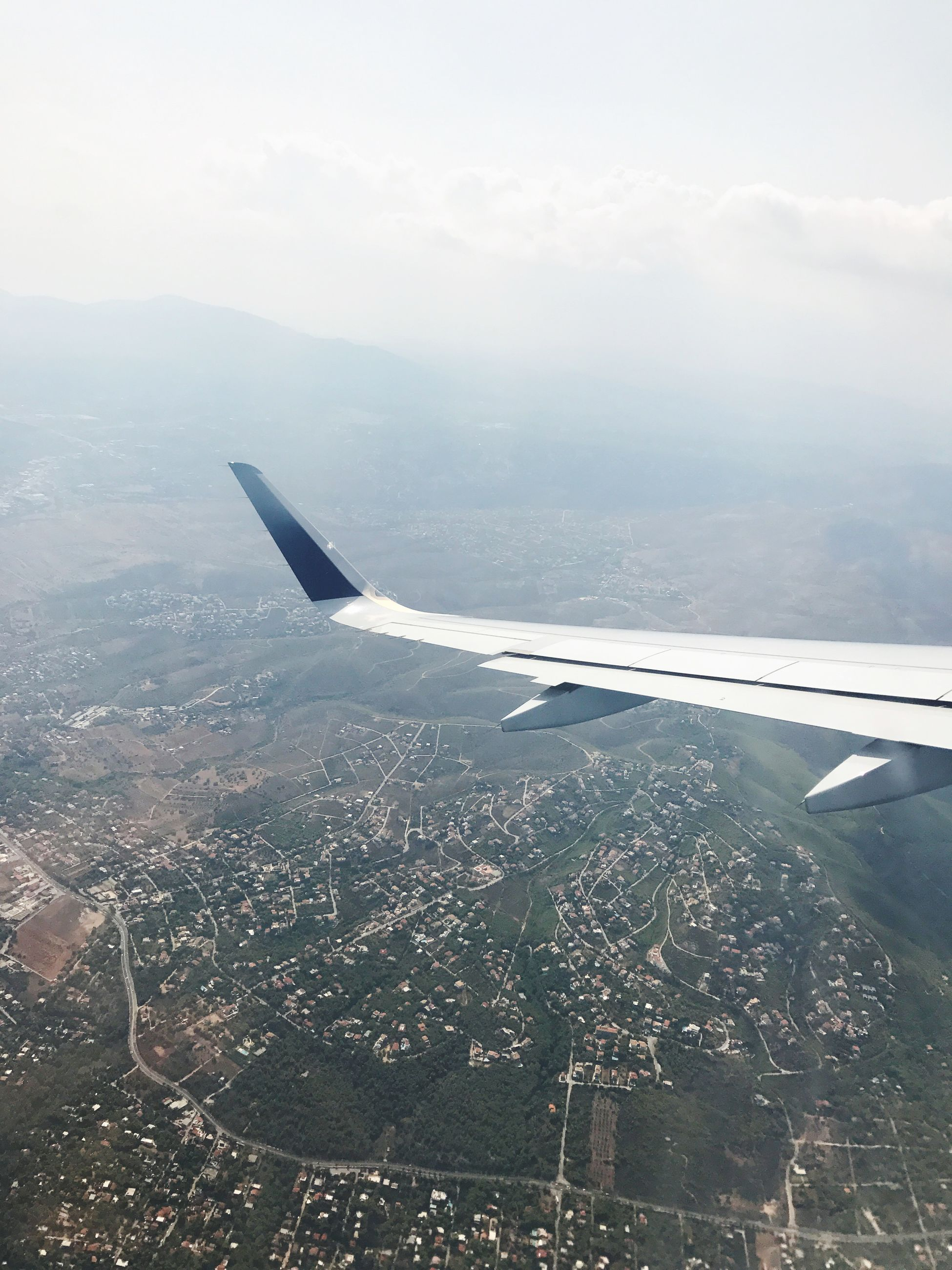 aerial view, airplane, airplane wing, nature, no people, sky, scenics, flying, landscape, aircraft wing, mid-air, transportation, day, air vehicle, cityscape, outdoors, beauty in nature, city, mountain
