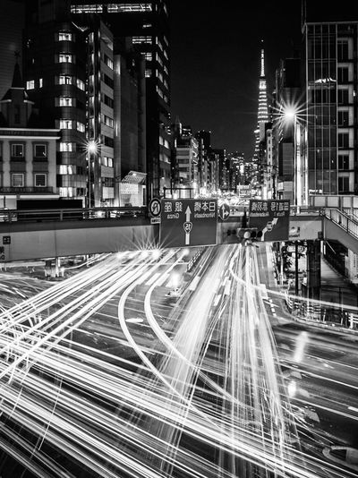 Light trails on road by buildings in city at night