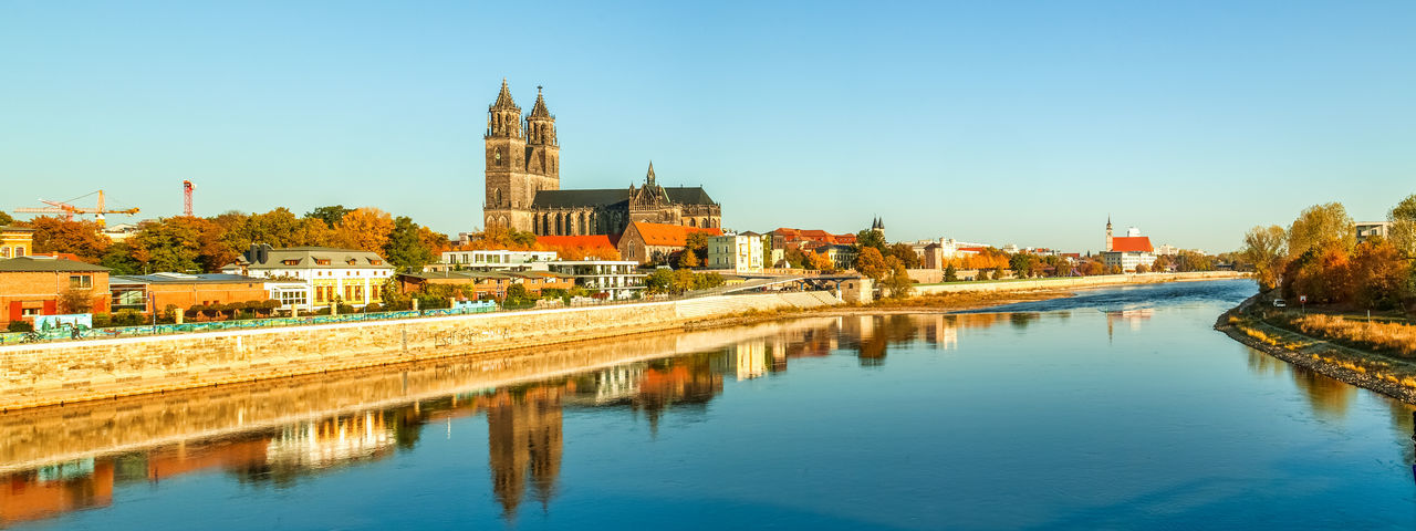 Panoramic view of cathedral by river against clear blue sky during sunset