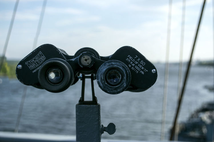 A set of binoculars on the flybridge of the USS Slater on the Hudson River, overlooks the river. Binoculars Close-up Focus On Foreground High Section Horizon Nautical Vessel Observation Point Outdoors Sea Ship Sky Surveillance