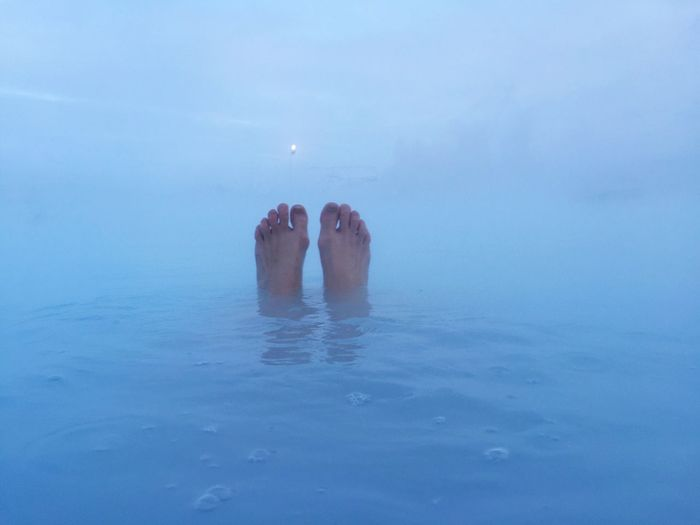 Low section of person relaxing in blue lagoon