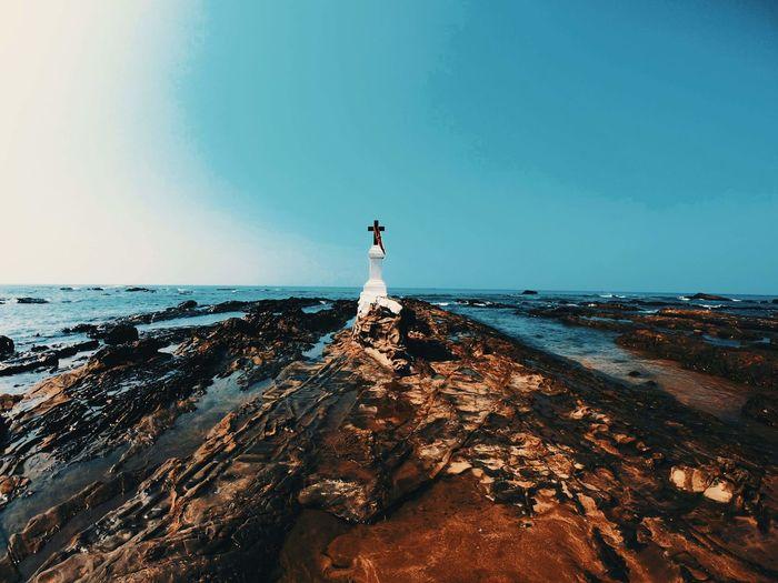 A christian cross on a rock by sea against clear sky